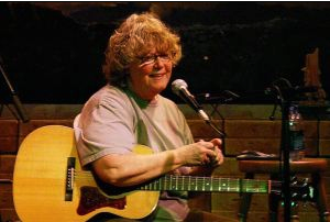 Picture of Cheryl Wheeler looking proud with an acoustic guitar